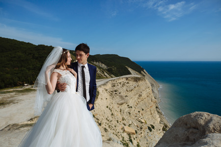 Groom in elegant suit and bride in white dress at weddingday on cliff with beautiful view of ocean Banco de Imagens - 117833726