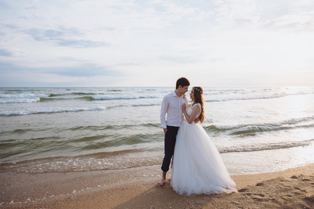 Beautiful young just marriied couple standing on ocean beach. Newlyweds spend time together, embrace and kiss Banco de Imagens