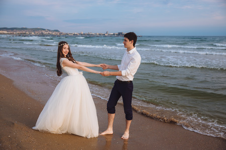 Happy loving couple newlyweds hold each others hands on ocean beach. Beautiful bride and groom at wedding day outdoors