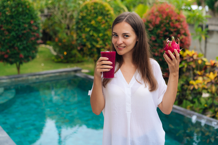 Portrait of beautiful young girl holding glass of dragon fruit smoothie and fruit in her hands near pool.