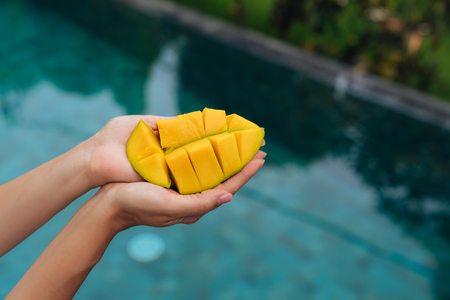 Close up slice of mango in female hands on background of blue swimming pool.