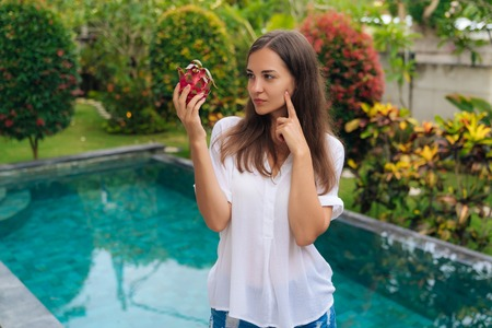 Portrait thoughtful girl with long hair holding dragon fruits, pitaya in her hand, thinking of eating or not eating it 写真素材