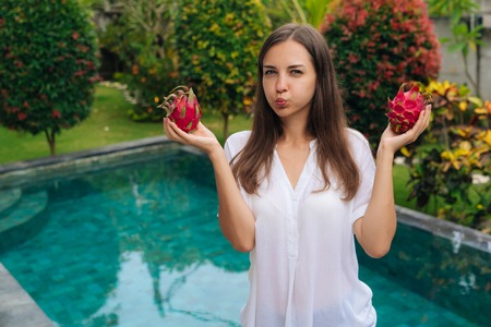 Portrait girl holds two dragon fruits, pitaya in her hands and makes funny face inflates her cheeks Banco de Imagens
