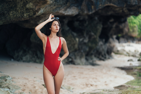 Portrait of sexy model in red swimwear and sunglasses posing on rocky beach