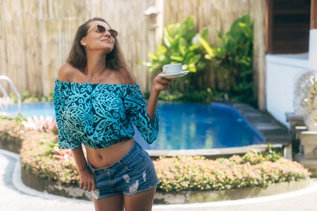 Beautiful brunette girl in sunglasses drinks coffee or tea and enjoys morning time near pool 免版税图像
