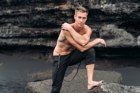 Sexy fitness male model in black pants and shirtless posing on black sandy beach.