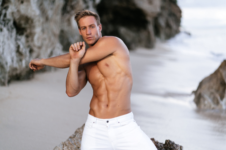 Sexy fitness male model in white pants and shirtless posing on tropical sandy beach