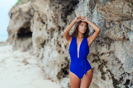 Sexy brunette girl in blue swimwear rests on white sand beach Stock Photo