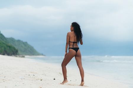 Vista trasera mujer afroamericana descansando y tomando el sol en la isla paradisíaca. Foto de archivo