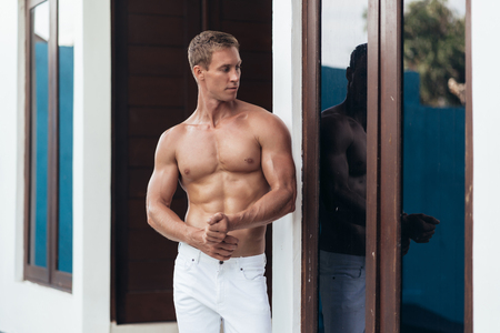 Muscular man with naked torso posing on camera, his silhouette reflected in window on background