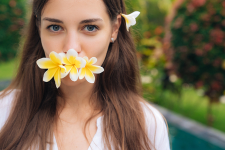 Portrait of lovely girl with natural make-up and plumeria, frangipani flowers in her mouth.