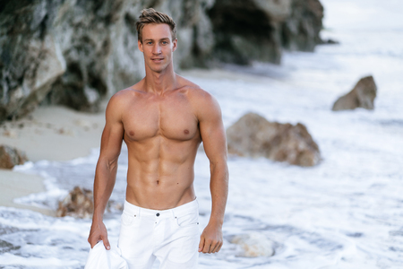 Portrait of tanned fit male model with a naked torso on the beach.