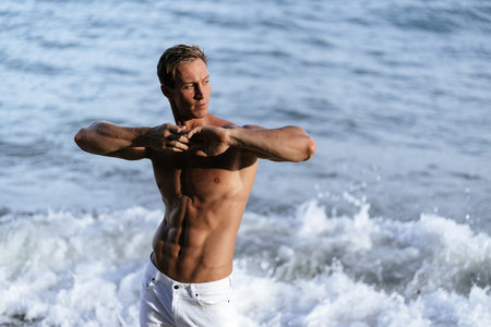 Beautiful man with naked muscular torso at white sand beach.