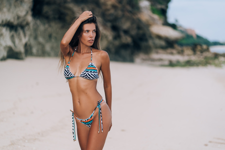 Beautiful sexy girl in swimwear walking on sandy beach with rock on background Imagens