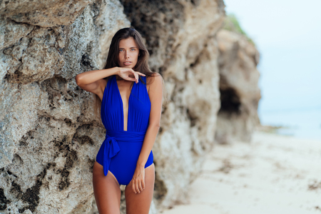 Beautiful tanned girl in blue swimwear posing on beach with rock on background
