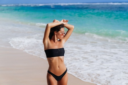 Beautiful girl in black swimsuit and sunglasses resting near ocean on beach Imagens