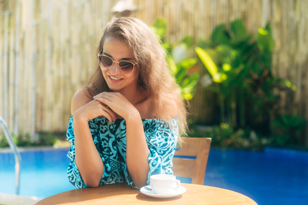 Happy tanned girl in sunglasses sits outdoors at table with cups of coffee or tea