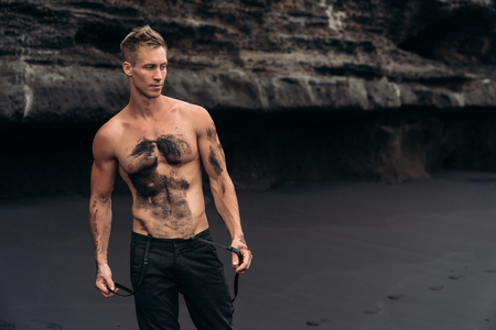Sexy fitness male model in black pants and shirtless posing on black sandy beach