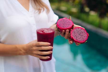Close up glass of dragon fruit smoothie and fruit in woman hands