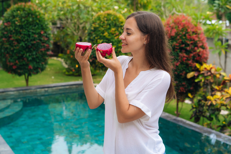 Happy beautiful girl holds two dragon fruits, pitaya in her hands, pool on background