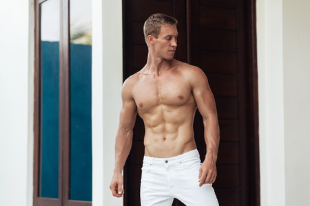 Muscular fitness model in white pants standing outdoors. Portrait of strong and handsome young man