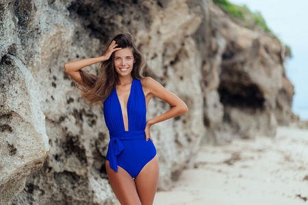 Slender sexy tanned woman in blue swimsuit posing on beach with white sand