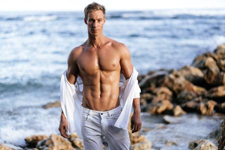 Gespierde atletische man in witte broek met een torso op het strand.