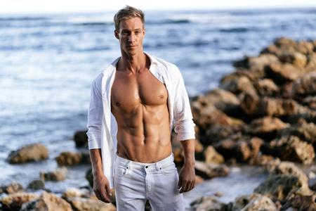 Muskulöser athletischer Mann im weißen Hemd mit nacktem Oberkörper ruht am Strand