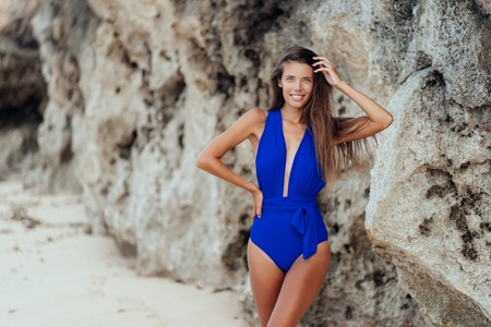 Beautiful smiling girl in blue swimwear posing on beach with rock on background