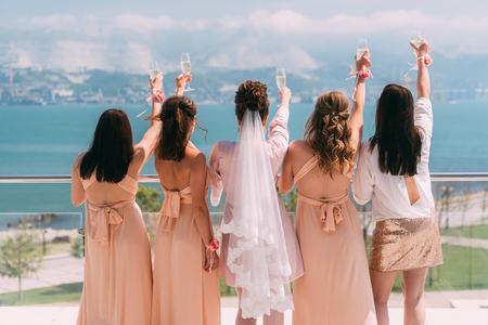 Backside view bride and girlfriends on balcony, raised glass of champagne Banco de Imagens - 124620669
