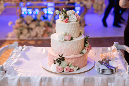 Big white wedding cake with pink roses on table