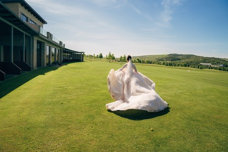 Backside view, bride runs in white wedding dress with veil on green field