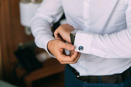 Close-up groom hands puts on cufflinks. Elegant gentleman clothers, white shirt Stock Photo