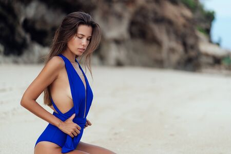 Slender sexy tanned girl in blue swimsuit posing on beach with white sand