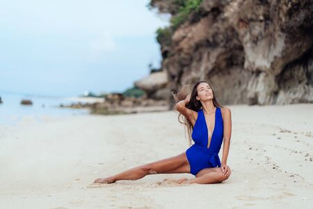 Beautiful tanned brunette girl in blue swimsuit siting on sandy beach Stock Photo