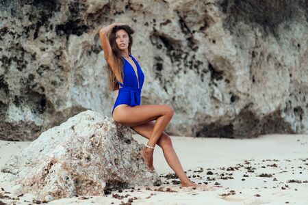 Beautiful sexy tanned woman in blue swimsuit on white sand beach