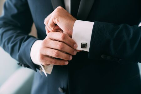 Close-up groom hands puts on cufflinks. Elegant gentleman clothers, white shirt