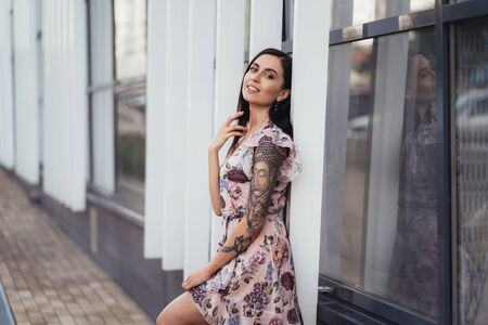 Beautiful happy young woman in colored dress posing near business center