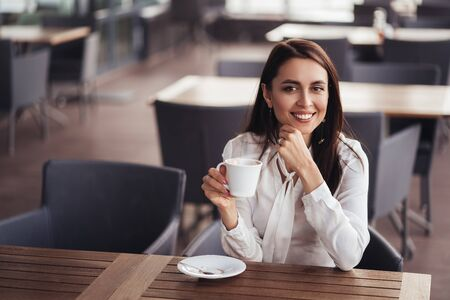 Beautiful business woman drinks coffee in cafe, lunches in cafe during her break Stock fotó