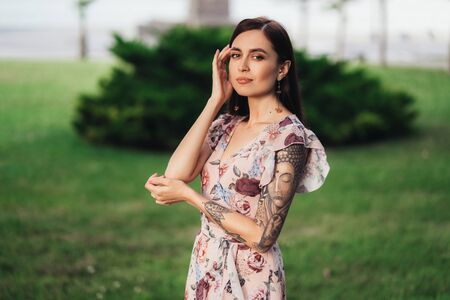 Girl with tattoo on her arm and in summer dress posing of greenery on background Stock fotó