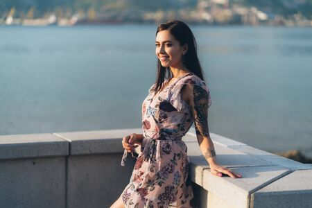 Beautiful smiling girl in summer dress posing in sunset time on waterfront