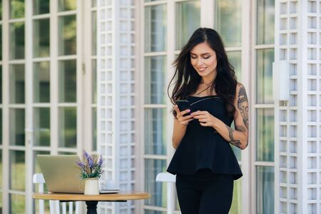 Girl freelancer with tattoo on her arm uses phone and laptop for work in cafe Stock fotó