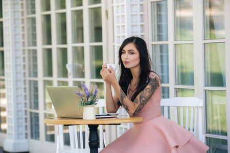 Beautiful girl freelancer drinks coffee in cafe, laptop and flowers on table