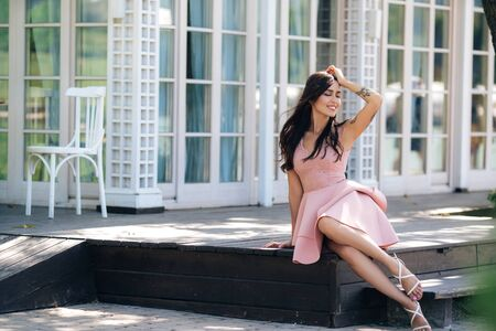 Beautiful smiling girl in pink dress sitting on wooden steps of street cafe Archivio Fotografico