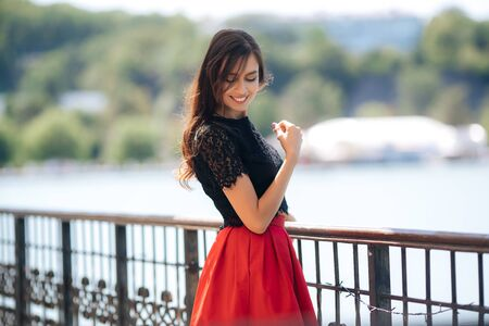 Beautiful happy girl posing outdoor wearing red skirt and black blouse