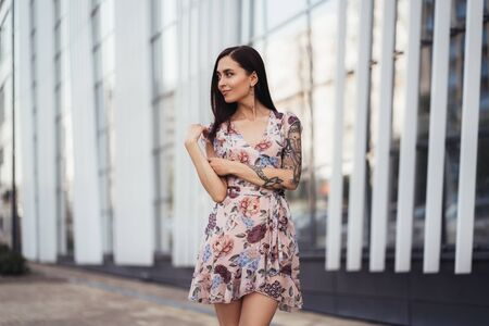 Attractive brunette girl in colored dress posing near modern building. Standard-Bild
