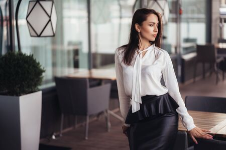 Business woman poses in cafe, beautiful girl rests during her break