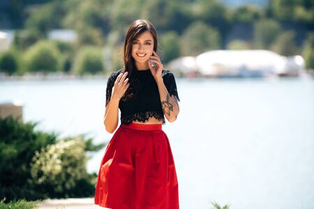 Stylish attractive girl with beautiful smile posing near lake on summer day Archivio Fotografico