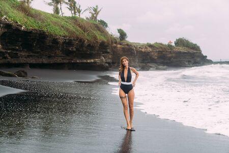 Girl with sexy body in swimwear walks on black sandy beach. Concept travel