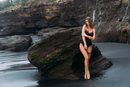 Sexy girl in swimsuit with tattoo on her leg poses near big stone on sandy beach Archivio Fotografico